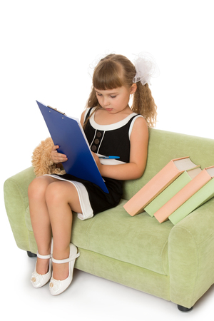 keen: Keen little girl sitting on the couch and writing pen in the folder - Isolated on white background Stock Photo
