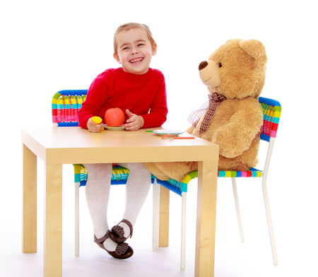 playing with spoon: A cheerful little girl, and big Teddy bear sitting together at the table - Isolated on white background