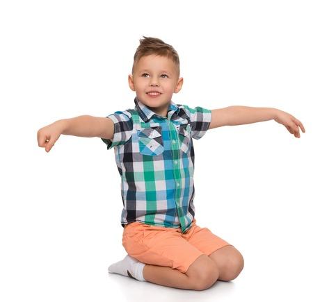 Grappig weinig blonde jongen zittend op de vloer op zijn knieën. De jongen sectie in de arm - die op een witte achtergrond Stockfoto