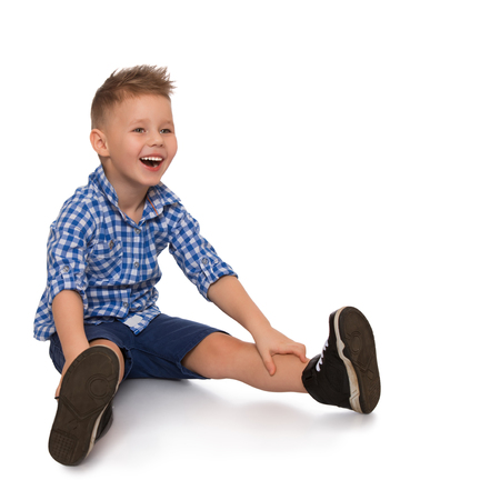 he laughs: Funny little blond boy sitting on the floor. He cheerfully laughs - Isolated on white background Stock Photo
