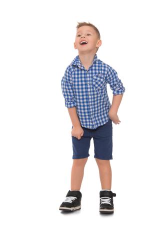 bermudas: niño rubio divertido en una camisa y pantalones cortos de mezclilla azul. Muchacho de la diversión se ríe - aislada en el fondo blanco Foto de archivo