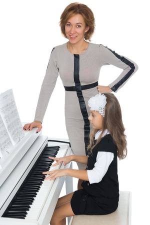 The girl at the music school diligently learn to play piano music , which gave her music teacher - Isolated on white background