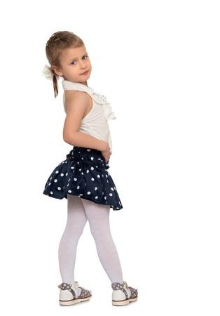 falda: Ni�a linda en la falda negro con lunares se est� convirtiendo los lados de la c�mara - aislada en el fondo blanco