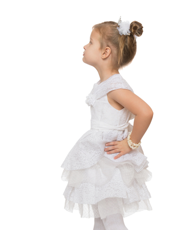 A little girl in a white dress standing resentfully turning the camera sideways. Close-up- Isolated on white background