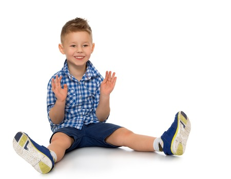 beautiful little boys: Little boy in shirt and shorts sitting on the floor and claps - Isolated on white background