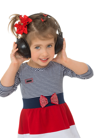 enthusiastically: A little girl enthusiastically listens to music through large headphones stereo black. Close-up- Isolated on white background