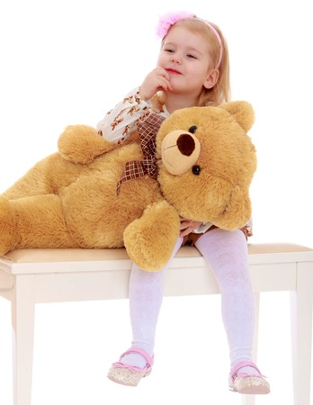 playing with spoon: Adorable little girl playing with a big Teddy bear - Isolated on white background