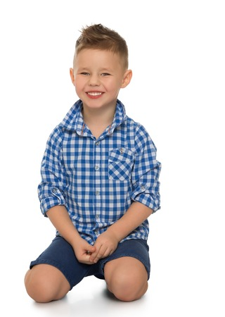 Fair-haired little boy in blue in a plaid shirt and blue shorts is kneeling on the floor.close-up - Isolated on white background