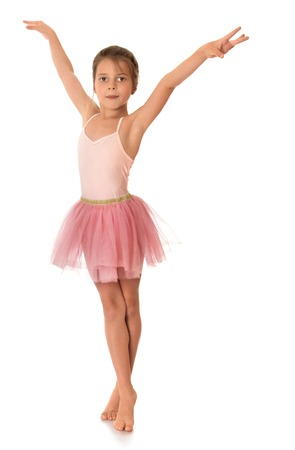 skirts: Slender ballerina girl in a light dress sports a pink color, standing on tiptoe barefoot - Isolated on white background Stock Photo
