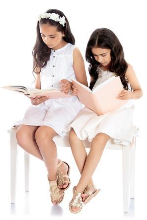jolie petite fille: Deux jolies filles aux cheveux noirs vêtus de robes blanches lu avec enthousiasme des livres assis sur un canapé blanc - isolé sur fond blanc Banque d'images