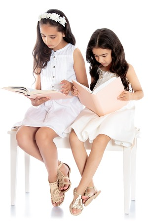 pretty little girl: Two pretty dark-haired girls dressed in white dresses enthusiastically read books sitting on a white couch - Isolated on white background Stock Photo