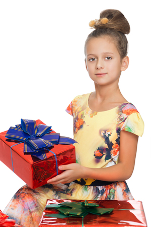 tied girl: Dressy girl children with beautiful hair on your head holds in his hands a beautifully wrapped box tied with a blue bow. Close-up - Isolated on white background