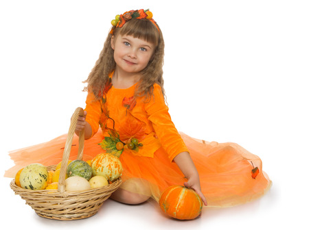 beautiful bangs: Beautiful little blonde girl with wavy , long, blond hair and short bangs on the head,in a bright orange dress sits on the floor with basket full of vegetables - Isolated on white background Stock Photo