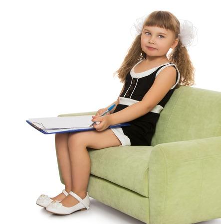 diligente: La ni�a hermosa colegiala diligente, sentado en el sof� y realiza una entrada con un l�piz - aislado sobre fondo blanco