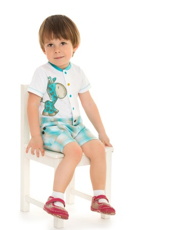 playgroup: Cute little blond boy sitting on white chair - Isolated on white background