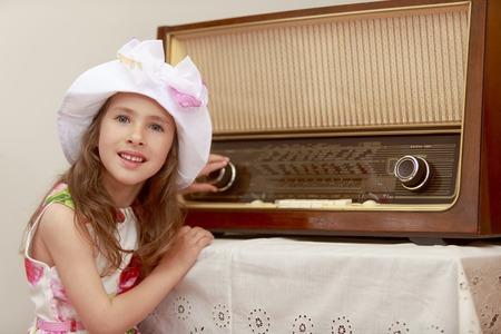 personas escuchando: Vestir niña gira la perilla de volumen en una radio antigua. Estilo retro