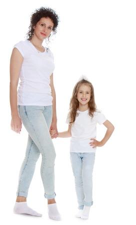 jeans apretados: , Madre esbelta joven hermosa y su pequeña hija en los mismos vaqueros ajustados y camisetas blancas - aislado en fondo blanco