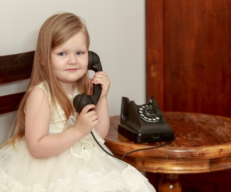 Small, round-faced girl with long blond hair attached to the ear-hook of vintage phone. Retro style