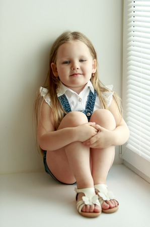 hugging knees: Cute little girl in denim shorts sits on the sill of the window, hugging her knees. Natural light from window Stock Photo
