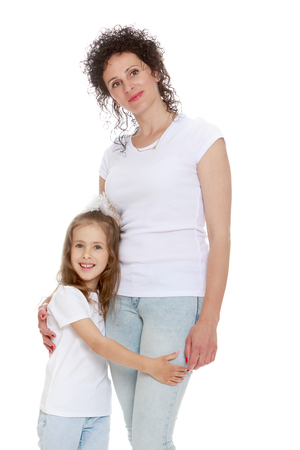 hugging legs: Beautiful mother and daughter in matching jeans and white shirts.Girl hugging moms legs - Isolated on white background Stock Photo