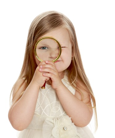 Funny little round-faced girl with long, blonde hair, looking at camera using a big magnifying glass . Close-up - Isolated on white background