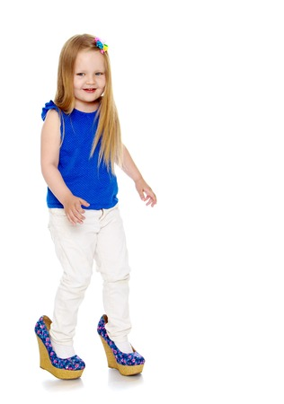 Happy little girl with long blond hair, put on the legs of moms shoes that she doesnt come in my size-Isolated on white background