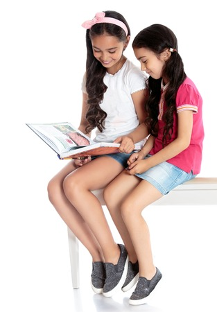 Two beautiful dark-haired girls girls in short denim skirts sit on the couch and read books - Isolated on white background