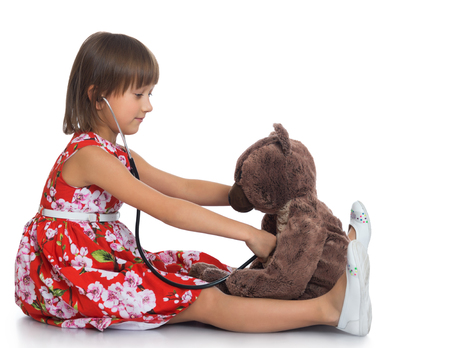 dressy: Dressy little girl playing with a Teddy bear in the hospital . the girl Listens to the bear stethoscope - Isolated on white background Stock Photo
