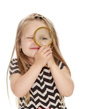 Grappig meisje kijkt door een vergrootglas. Close-up - geïsoleerd op een witte achtergrond Stockfoto