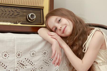 Petite fille à l'écoute de la musique à travers une vieille radio