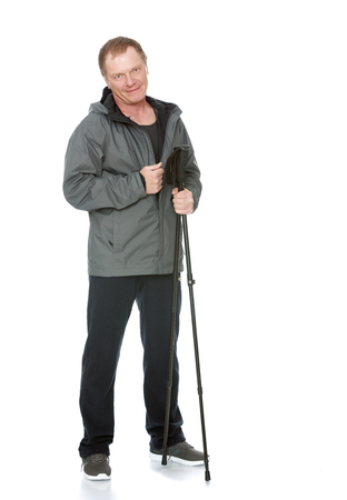 relies: A 50 year old man in a track suit , relies on sticks for Nordic walking-Isolated on white background