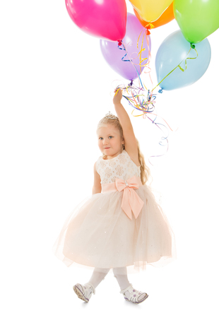 Funny little girl in fancy white dress holding a balloons - Isolated on white background Фото со стока