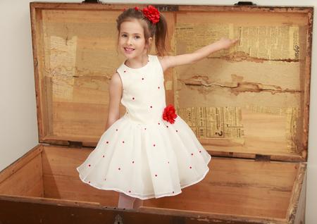 oude krant: Mooi meisje in mooie witte jurk speelt in de kofferbak van de oude grootmoeder. Meisje toont een vinger op een oude krant die werd geplakt om het deksel.