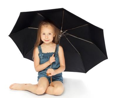 umbrela: Cute little girl sitting on the floor under a big black umbrella - Isolated on white background