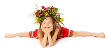 swimming costumes: Adorable little girl in a bright red dress with a large floral wreath on his head. Girl does the splits-Isolated on white background