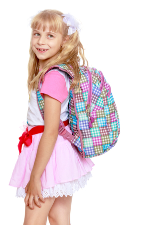 Cheerful little girl in a pink short skirt with a knapsack on his shoulders. Close-up-Isolated on white background Stock Photo