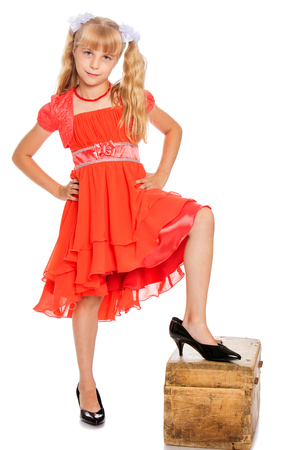 big shoes: Fashionable little girl with long, blonde ponytails on her head in a bright orange dress . Feet girl high-heeled shoes.-Isolated on white background Stock Photo