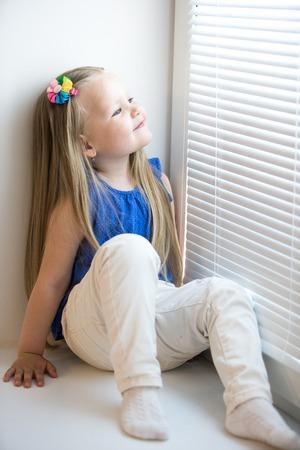 Nettes kleines Mädchen mit langen blonden Haaren unter den Schultern. Im blauen Hemd und weiße Jeans sitzt auf der Fensterbank. Mädchen schaut aus dem Fenster