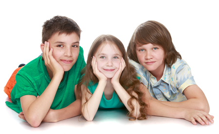 looking directly at camera: Three children lie on the floor and looking directly at the camera - Isolated on white background Stock Photo