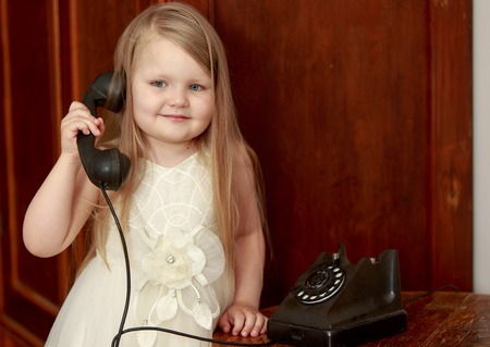 chubby girl: Cute little chubby girl with long, blonde hair below the shoulders, holds up the old phone
