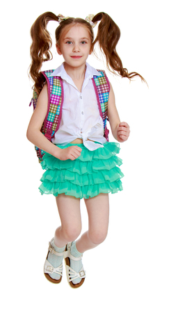 without legs: Joyful little girl with long hair to the waist which wire braided white ribbons. In a white shirt without a pattern and green short skirt. Girl jumping with legs tucked under . Stock Photo