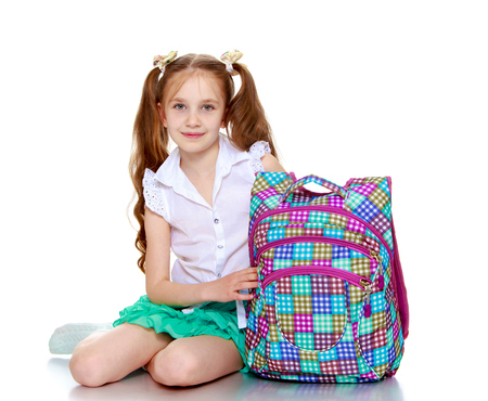uniforms: Cute little girl in a short green skirt and white blouse holding a school bag-Isolated on white background Stock Photo