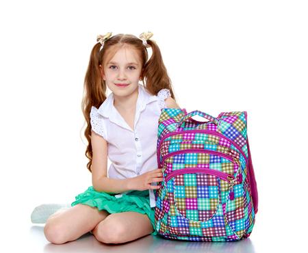 uniformes: Niña linda en una falda corta verde y una blusa blanca que sostiene una escuela-Bolso aislado en el fondo blanco