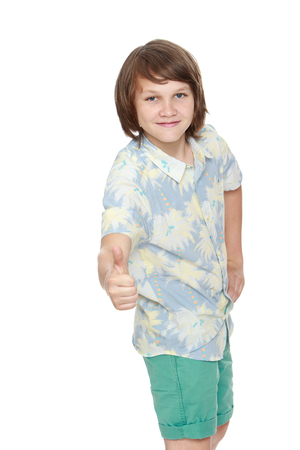 his shirt sleeves: Portrait of a smiling boy in shorts and shirt with short sleeves. The young man raised his thumb to the top. Close-up  - Isolated on white background