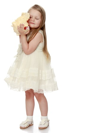 Lovely little round-faced girl with long, blonde hair below the shoulders, in a white dress. Girl put your ear to a large sea shell. She listens to the sound of the sea - Isolated on white background