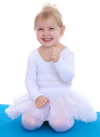 gym dress: Joyful little girl , a future gymnast, white sports dress kneeling on a blue gym Mat-Isolated on white background