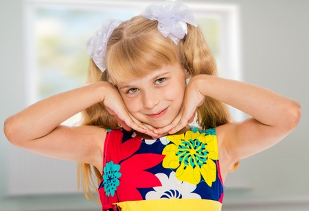 ponytails: Sweet, adorable little girl with long blonde ponytails on her head tied with white bows. Close-up-Isolated on white background Stock Photo