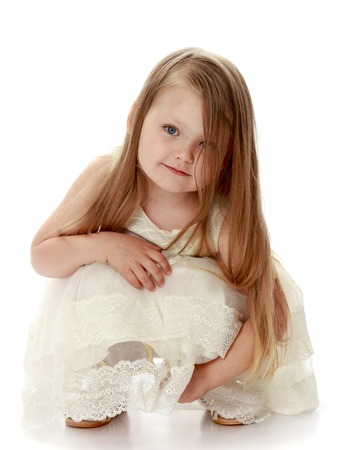 Lovely little round-faced girl with long, blonde hair below the shoulders, in a white dress. The girl squatted - Isolated on white background