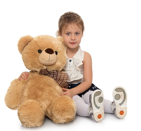 Cute little girl hugging a big Teddy bear . Girl sitting on the floor - Isolated on white background Stock Photo