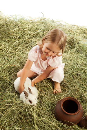 hayloft: Cute little girl is playing in the hayloft with rabbit-Isolated on white background